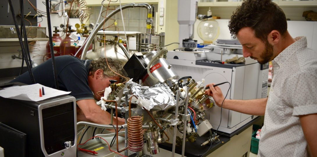 Two people working on lab equipment.