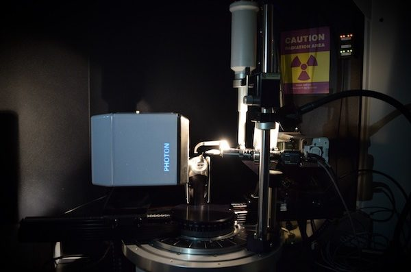 X-ray crystallographer machine with a brightly lit sample, in a very dark room.