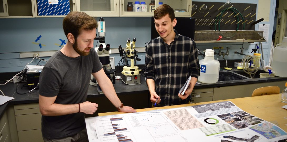 2 male students studying a large map/poster in a lab.