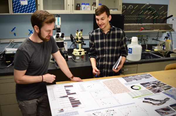 Two male geoscience students standing in a laboratory looking at a scientific poster on a table.