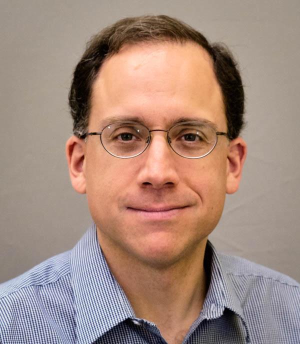 Portrait Headshot of Greg Keller. Man with short brown hair and glasses.
