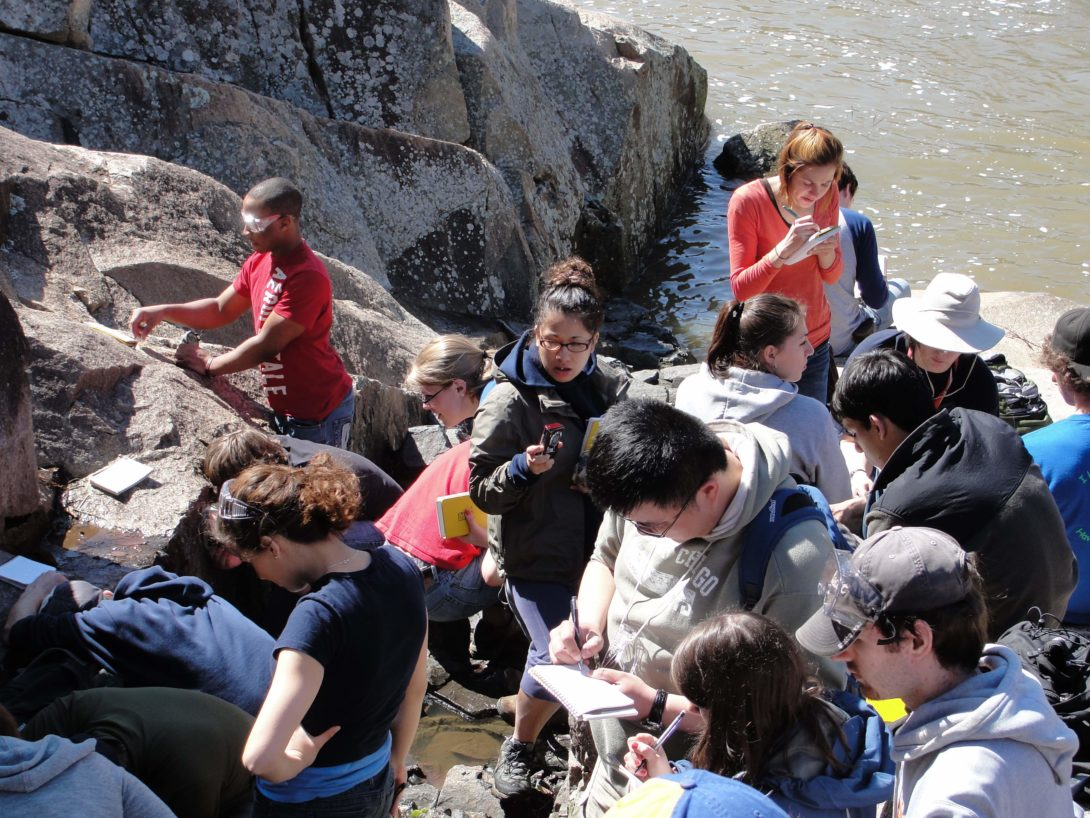 Group of students looking at rock outcrop along a river