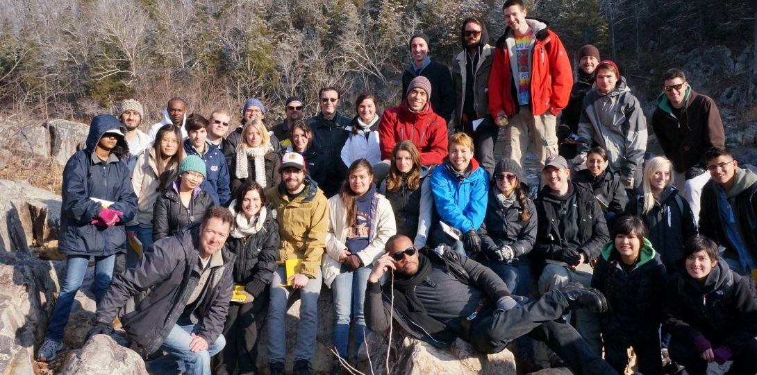 Group photo of geoscience and Earth science students sitting on rocks with trees in the background.