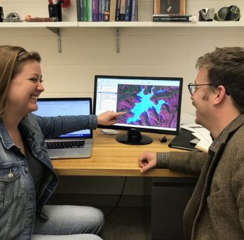 Geology undergraduate student and professor talking to each other in front of laptop and monitor displaying glacier data