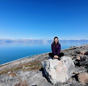 Cynthia sitting on a rock along the artic circle.  There is lake water and mountains in the background.