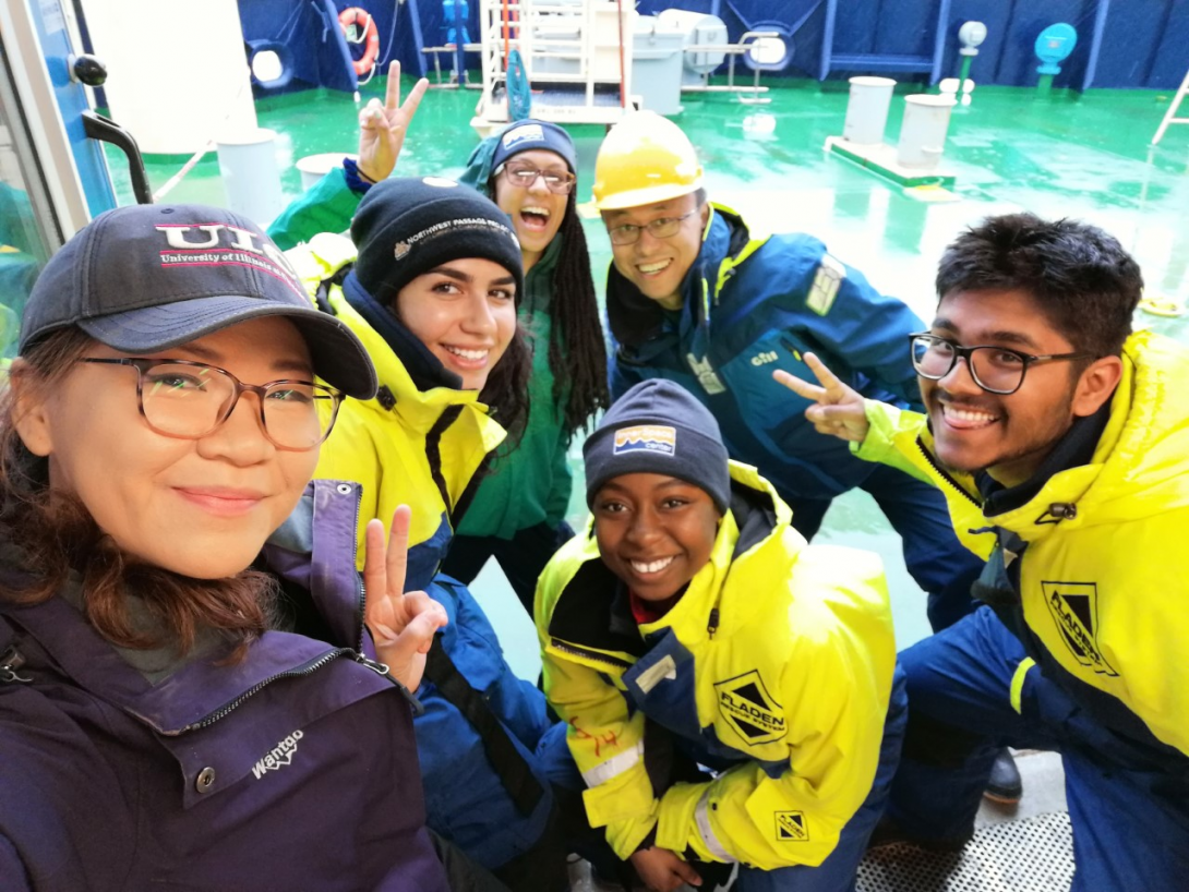 Group of 6 students  in front of lab equipment. Students are dressed with hats and big jackets.
