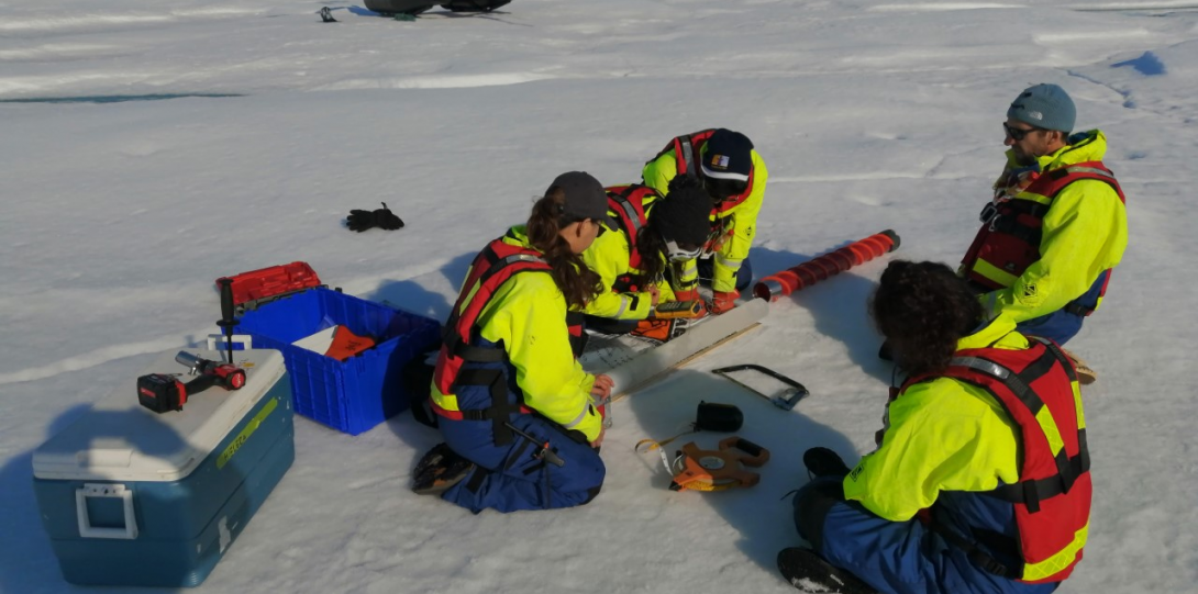 Students outside on a glacier taking an ice core with equipment