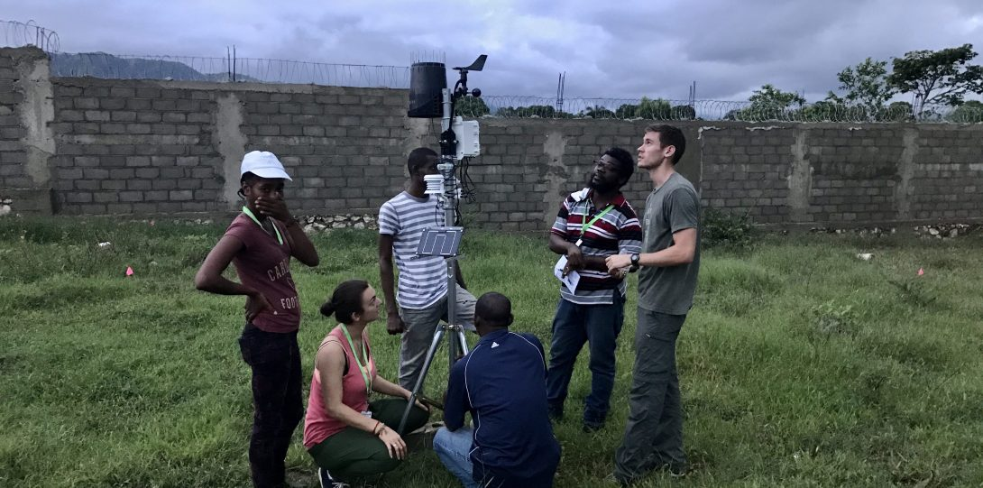 Group of scientists looking at a meteorological station