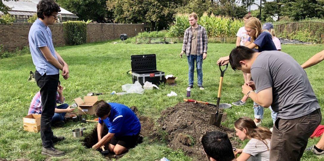 Group of geoscience students digging a hole in a grassy field