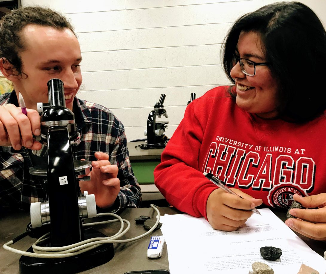 Geoscience students in class with microscopes