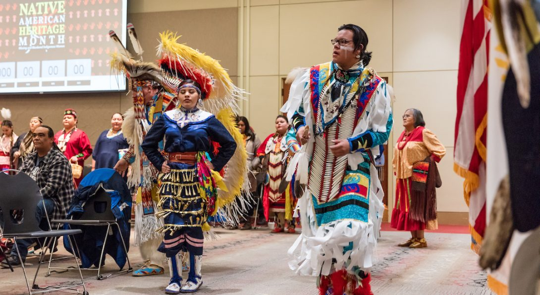 Colorfully dressed performers in traditional indigenious attire. Six performers are outside standing about 4 feet from each other.