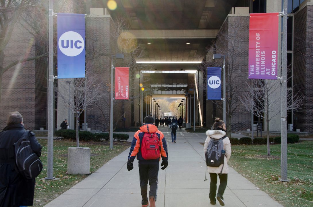 Students outside walking in between two buildings.  UIC in blue and red ombre are on the sides of the sidewalk
