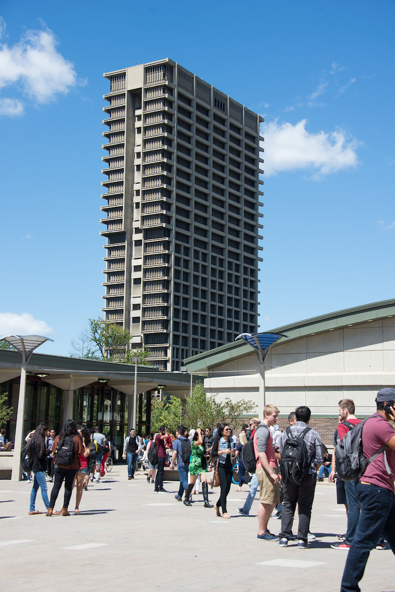 Tall concrete building, UIC's University Hall, with blue sky in the background and students in foreground.